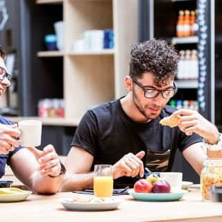 Two young men laughing while having healthy breakfast in a hotel