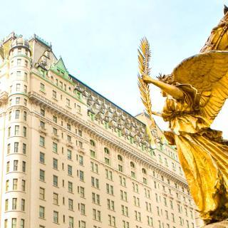 A Fairmont hotel from the outside, next to a golden statue