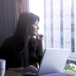 Woman sitting in front of laptop with cup of tea smiling looking view through sunny window