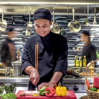 One man chef smiling cutting colorful fresh vegetables in the kitchen two cooks walking behind him
