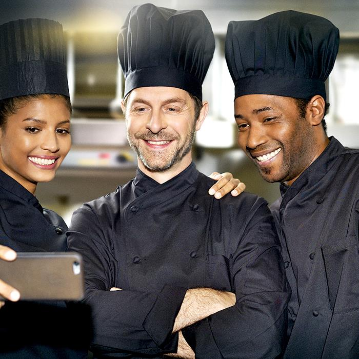 Three employees chef kitchen smiling taking together selfie on smartphone
