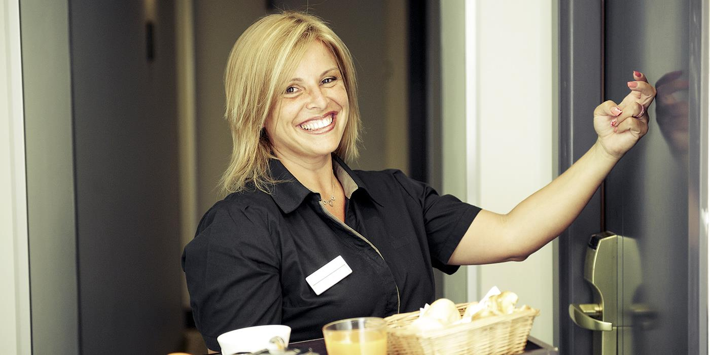 Woman Employee Knocking On Door Room Hotel Smiling Holding Breakfast Tray