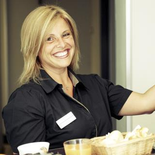 Woman employee knocking on door room hotel smiling holding breakfast tray
